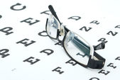 Glasses with eye chart isolated on white — Stock Photo
