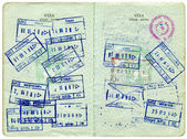 Visa entry and exit stamps in a passport — Stock Photo
