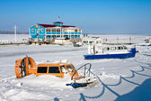 Hovercraft on the bank of frozen river against blue sky — Stock Photo