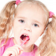 Little cute girl in studio brushing teeth — Stock Photo