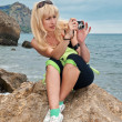 Girl with a camera on seacoast — Stock Photo