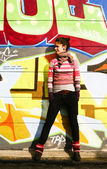 Jonge vrouw met een graffiti-achtergrond — Stockfoto