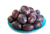 Plums in plate on white background — Stock Photo