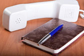 Telephone with a notebook and pen — Stock Photo
