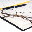 Stock Photo: Pen glasses and notebook