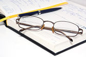 Pen glasses and notebook — Stock Photo