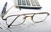 Glasses, pen and calculator. Focus on glasess — Stock Photo