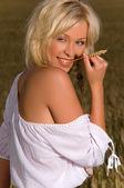 美丽金发女郎坐在小麦的字段上 — 图库照片
