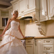 Stock Photo: Bride stands in kitchen