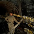 Miner works in a mine - Stock Photo