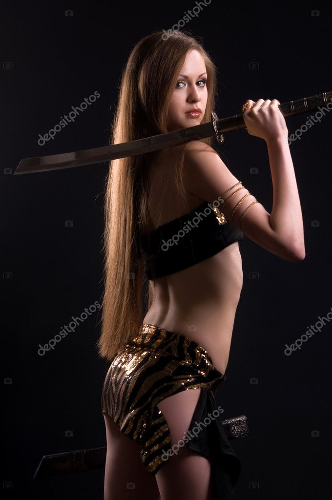 A beautiful woman with a sword in the studio on a black background  Stock Photo #4203061