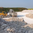 Stock Photo: Excavator loads truck on gravel