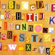 Colorful alphabet with letters torn from newspapers - Stock Photo