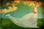 Beauty young woman in white dress on the green meadow — Stock Photo