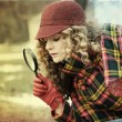 Young woman with magnifier glass and hat - Stok fotoğraf