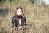 The girl-teenager sits on a meadow — Stock Photo