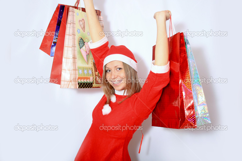 A portrait of a beautiful caucasian christmas santa girl carrying shopping bags  Stock Photo #4598478