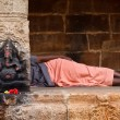 Man sleeping behing the column with Ganesha images. in Hindu tem - Stock Photo