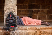 Man sleeping behing the column with Ganesha images. in Hindu tem — Stock Photo
