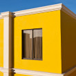 Yellow house and blue sky - Stock Photo