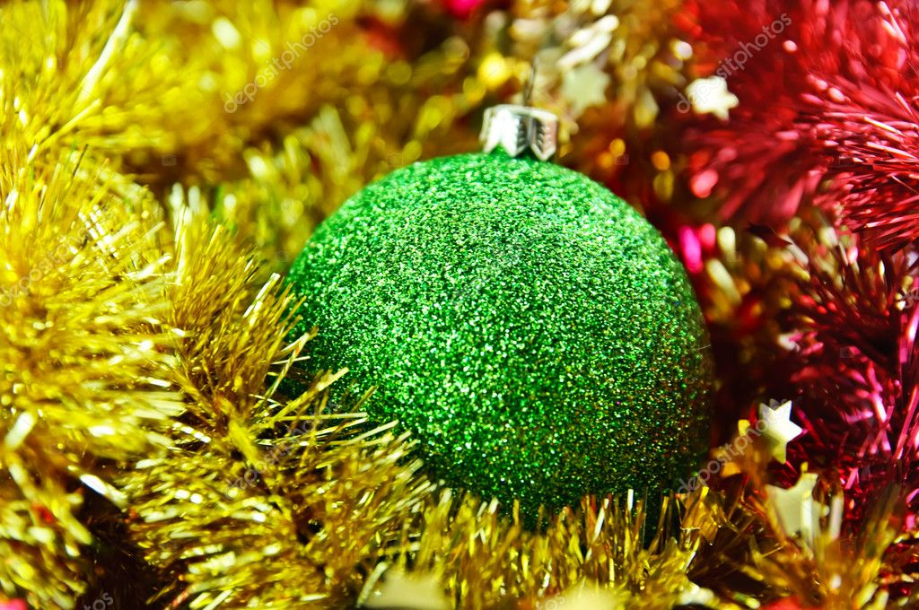 Christmas green ball over shiny red and yellow  tinsel — Stock Photo #4292125