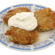 Potato fritters with sour cream - Stock Photo