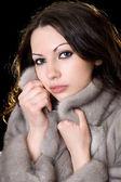 Jonge mooie vrouw in een bontjas — Stockfoto