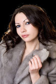 Young pretty woman in a fur coat — Stock Photo