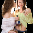 Portrait of the two girlfriends with a cognac bottle — Stock Photo