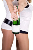 Two girls with a champagne bottle. Isolated — Stock Photo