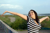 Happy young woman with arms raised outdoors — Stock Photo