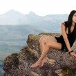 Pretty girl sits on a rock — Stock Photo #4906479