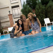 Young man and two girls drink champagne in pool - Stock Photo