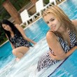 Two playful girlfriends in pool — Stock Photo
