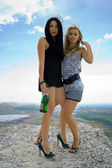 Two young women with a champagne bottle — Stok fotoğraf