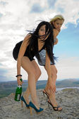 Two girls with a champagne bottle — Stok fotoğraf