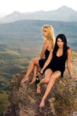 Two young women with a champagne bottle sit on a rock — Stok fotoğraf
