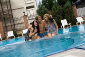 Young man and two girls drink champagne in pool — Stock Photo