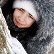 Beautiful girl near a tree in snow. - Stockfoto