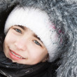 Portrait of the beautiful girl in a fur hood in snow. — Stock Photo