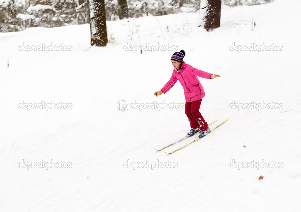 Little girl skiing fast down the hill in snow winter day  Stock Photo #4801706