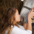 Stock Photo: Young girl kissing horse on nose