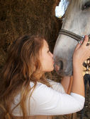 Young girl kissing a horse on the nose — Stock Photo