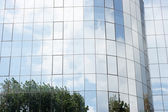 Modern building glass reflects nature of trees and clouds — Stock Photo