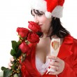Woman in a red suit and hat of Santa Claus with red roses and ch - Stock Photo