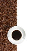 Coffee mug against the backdrop of coffee beans — Stock Photo