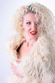 Curly blonde in a white fluffy fur coat — Stock Photo
