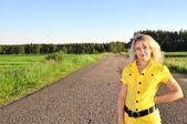 Giovane donna sorridente con sulla strada vuota — Foto Stock