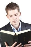 Jeune homme en costume tenant une bible — Photo