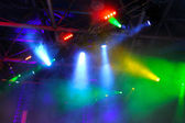 Colored spotlights on ceiling in smoke — Stock Photo
